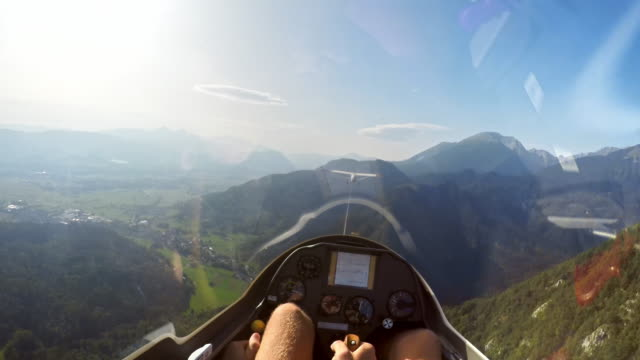 POV Pilot in the cockpit of a glider being towed above the green landscape in sunshine