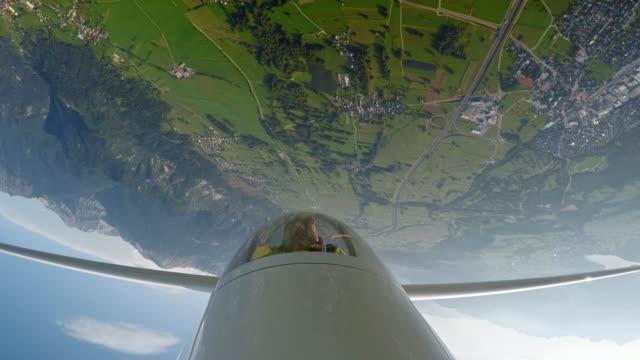 vidéos et rushes de ld pilote dans le cockpit d'un planeur tourner à l'envers au-dessus de la campagne ensoleillée - glisser
