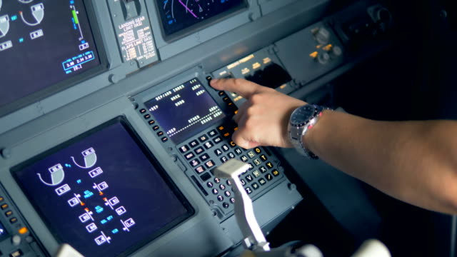 Pilot is entering data into airplane control system. video