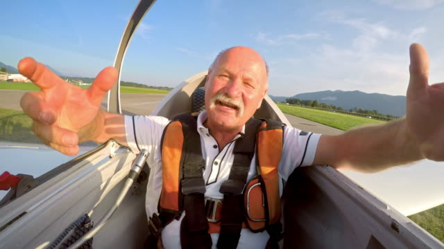 LD Pilot opening his cockpit after landing his glider and laughing in sunshine