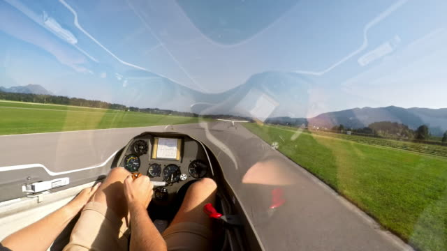 POV Pilot sitting in the cockpit of a glider holding the control stick while being towed into the air