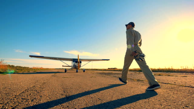 A pilot walking on an airfield to check an airplane, close up. Man walks on a runway and checks a plane. propeller airplane stock videos & royalty-free footage