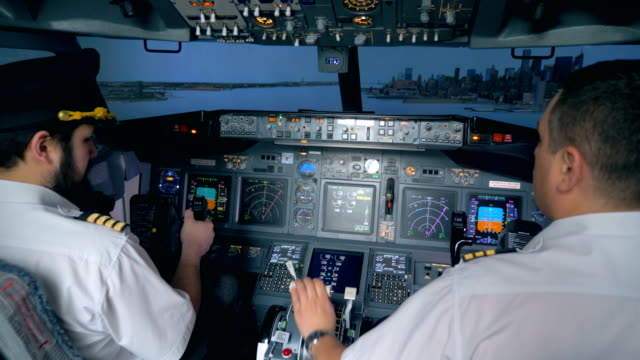 Pilots control an airbus in a flight simulator. One pilot holds a helm, while another pilot pushes buttons. landing touching down stock videos & royalty-free footage