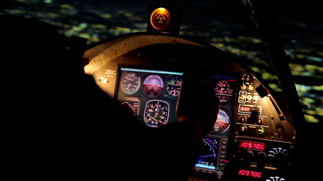 Pilot's hands on steering wheel, night flight, airplane hovering above city video