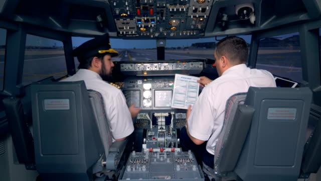 Pilots read a manual in a cockpit of a flight simulator. 4K. Pilots read a manual in a cockpit of a flight simulator. handbook stock videos & royalty-free footage