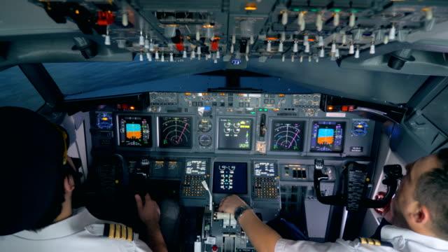 Pilots sit in a flight simuator, close up.