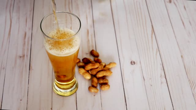 Pilsner beer pouring into glass and peanuts