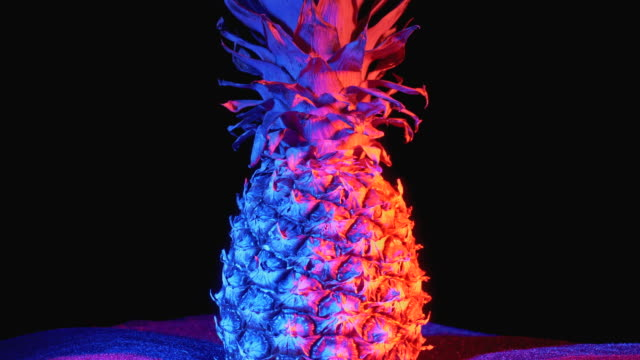 Pineapple with Red and Blue Backlight Rotates on a Black Background