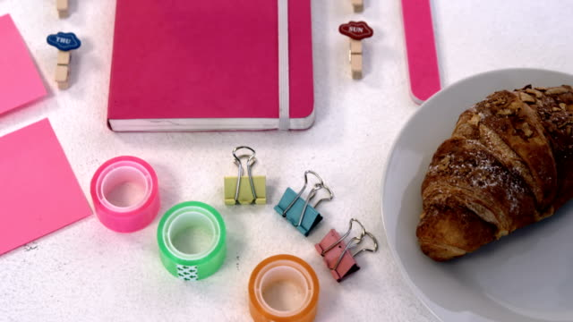 Pink accessories, croissant and stationery items on white background 4k video