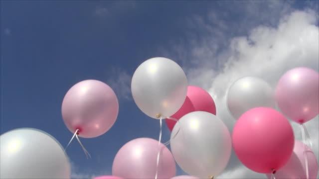 rosa och vita uppblåsbara bollar på tråden svänga av vinden mot himmel och moln - inflatable ring bildbanksvideor och videomaterial från bakom kulisserna