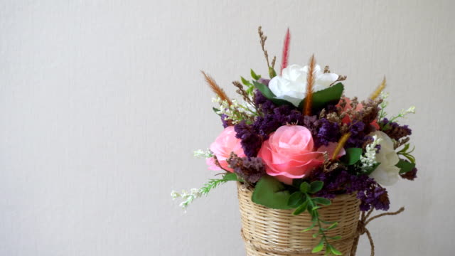 Pink and white roses flowers in woven wooden vase with small decorative leaves and small flowers on white background is rotating. Pastel flower collection presentation