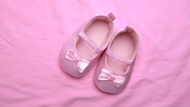 Pink baby booties on pink blanket Pink baby booties on revolving pink blanket surface baby booties stock videos & royalty-free footage