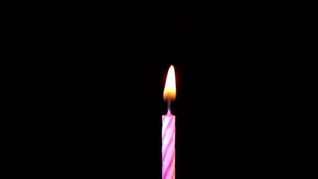 Bидео pink birthday candles light on isolated black