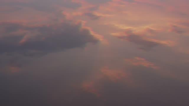 rosa moln reflekteras i vattnet. kreativ bakgrund - pink sunrise bildbanksvideor och videomaterial från bakom kulisserna
