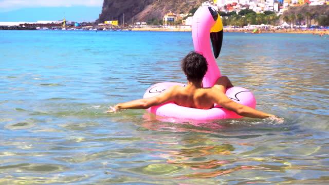 rosa flamingo på stranden - inflatable ring bildbanksvideor och videomaterial från bakom kulisserna