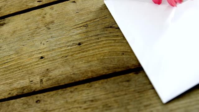Pink flower in envelope on wooden plank video