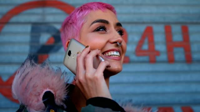 stockvideo's en b-roll-footage met roze haar vrouw praten op mobiele telefoon buiten winkel 4k - roze haar