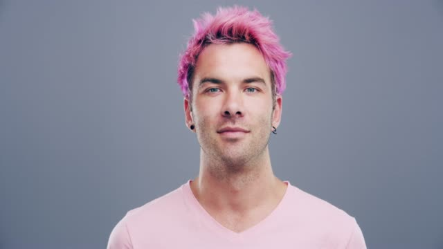 Pink makes me happy 4k video footage of a cheerful young man posing against a grey background vanity stock videos & royalty-free footage
