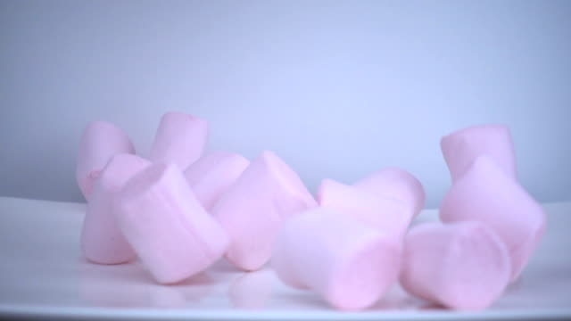 pink marshmallows falling in slow motion. - lanuginoso video stock e b–roll