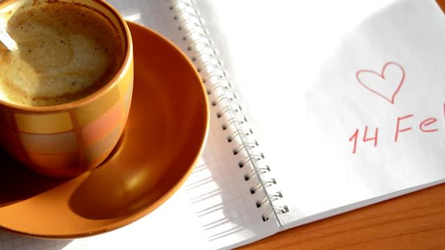 rosa pappershjärtan faller på öppna boken med inskriptionen den 14 februari, efter en kopp kaffe, selektiv fokus - lucia bildbanksvideor och videomaterial från bakom kulisserna