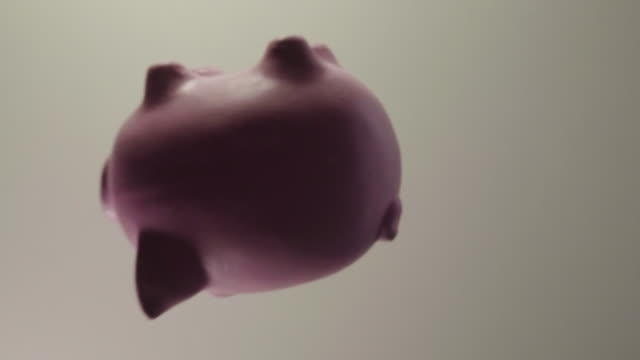 top view: pink pig money box with many golden coins falls on a table and breaks - slow motion - bankruptcy stock videos & royalty-free footage