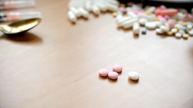 Pink pills man fingers moving, medical concept