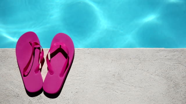 Pink slippers near swimming pool video