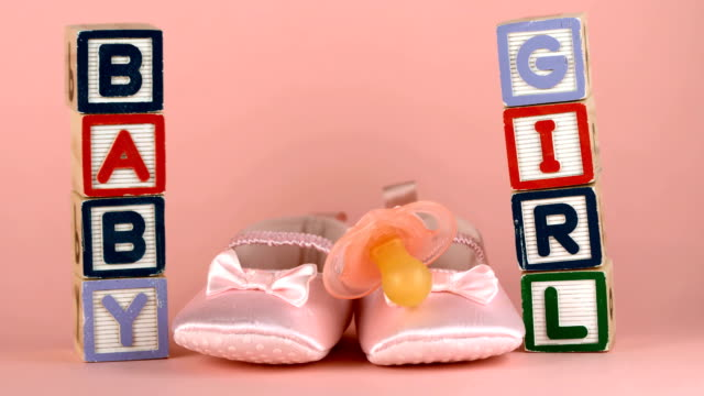 Pink soother falling in front of baby shoes and blocks Pink soother falling onto baby shoes besides baby blocks in slow motion baby booties stock videos & royalty-free footage