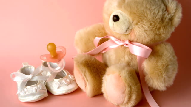 Pink soother falling in front of baby shoes and teddy Pink soother falling in front of baby shoes and a teddy bear in slow motion baby booties stock videos & royalty-free footage