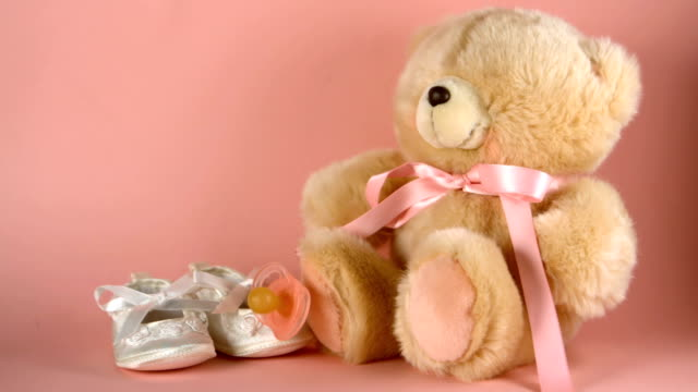Pink soother falling onto a teddy bear and baby shoes Pink soother falling onto a teddy bear and baby shoes in slow motion baby booties stock videos & royalty-free footage