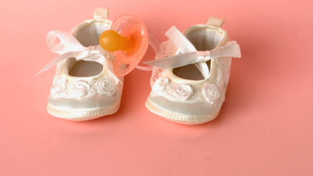 Pink soother falling onto baby shoes Pink soother falling onto baby shoes in slow motion baby booties stock videos & royalty-free footage