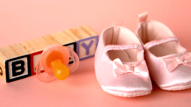 Pink soother falling onto booties Baby pacifier falling onto booties in front of wooden letters in slow motion baby booties stock videos & royalty-free footage