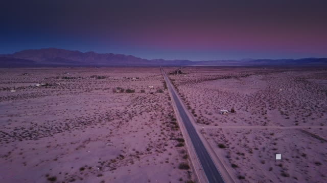 Pink Sunset Over the Desert - Drone Shot Drone flight over a road across the open desert near Twentynine Palms, California after sunset. mojave desert stock videos & royalty-free footage