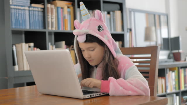 pink unicorn hooded mane girl studies on a laptop next to a bookstore