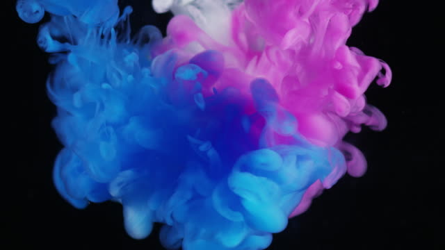 Pink White And Blue Ink Dropped In Water Black Background Stock