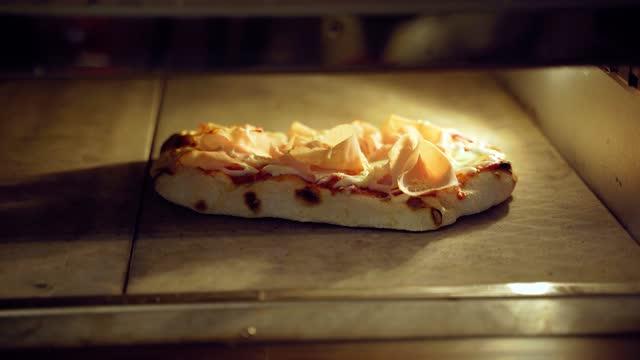 stockvideo's en b-roll-footage met pinsa romana gastronomische italiaanse keuken op zwarte houten achtergrond. scrocchiarella traditioneel gerecht. eten bezorgen bij pizzeria. pinsa met vlees, rucola, olijven, kaas. - dikke pizza close up