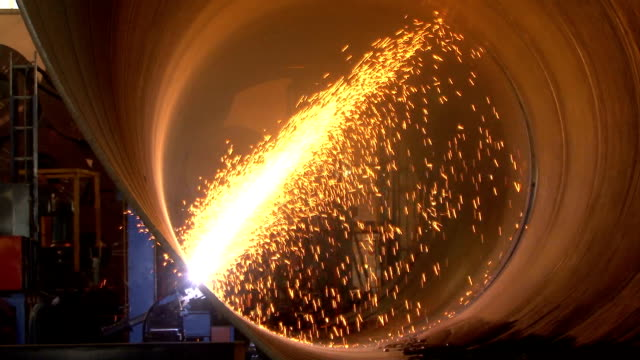 Pipe Cutting A spectacular shower of sparks as a large steel pipe is cut off from the coiling mill. civil engineering stock videos & royalty-free footage