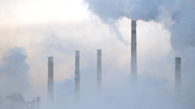 Pipe of a large plant smokestack in the fog