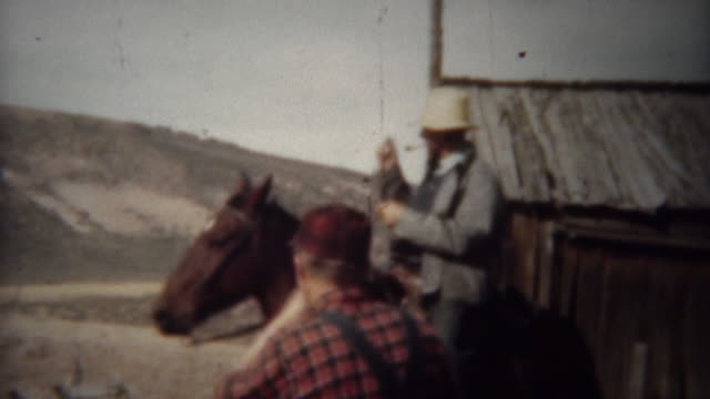 1940: Pipe smoking cowboy and wife riding horses on the range. video