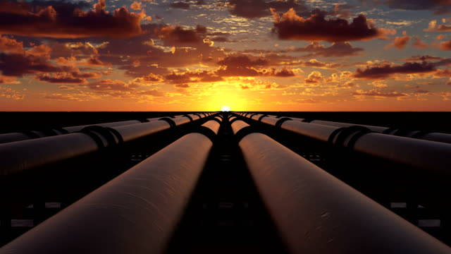 Pipeline transportation of oil, natural gas or water through metal pipes. Concept of the oil refining industry. The camera moves over six pipeline streams right at sunset