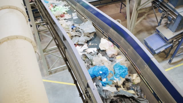 Pipelines and Conveyor Belt Inside Recycling Facility High angle view of pipelines and recyclables traveling by conveyor belt through waste management facility. manufacturing equipment stock videos & royalty-free footage