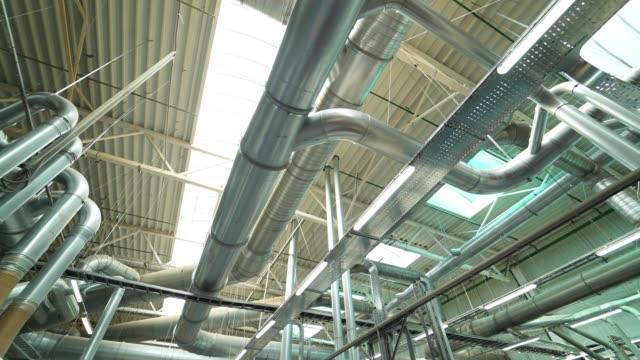 rör av ventilationssystemet ligger på taket av anläggning med tillverkning av parkettgolv. - ventilation bildbanksvideor och videomaterial från bakom kulisserna