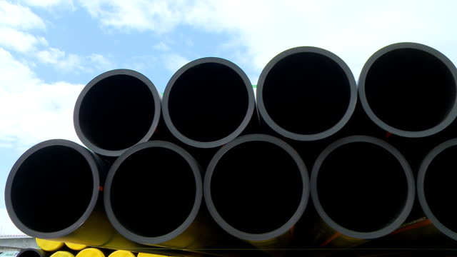 Pipes stacked in construction site dolly shot Pipes stacked in construction site dolly shot gas pipe stock videos & royalty-free footage