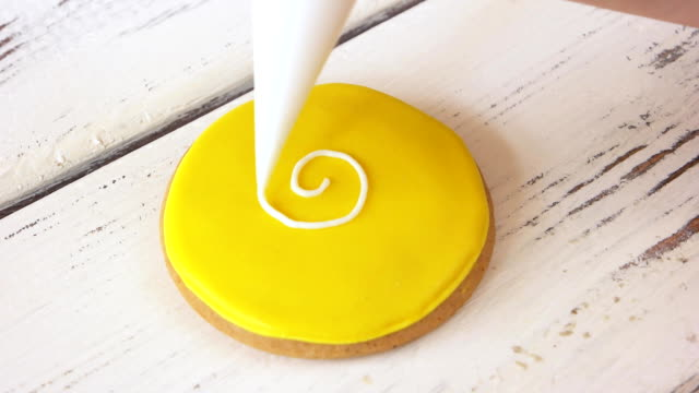 Piping a pattern on round yellow cookie.