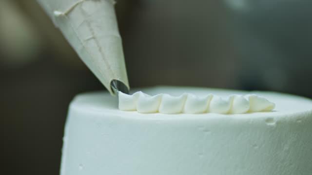vídeos de stock e filmes b-roll de piping frosting onto cake - bolos