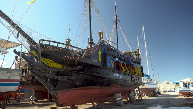 A pirate ship is under restoration. An old black ship stands on land.