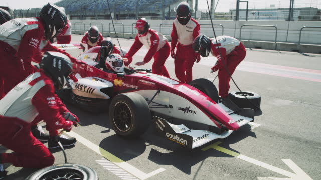 Pit crew repairing racecar during motorsport event