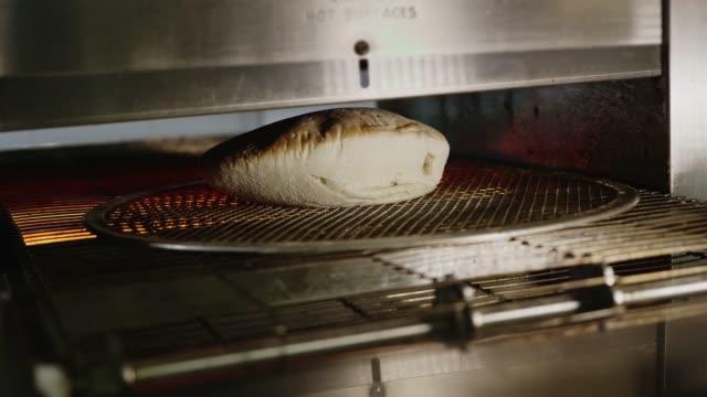 Proceso en el horno de panadería de pita. Pan de pita en el horno. Elaboración de pan. Pita de la hornada. - vídeo