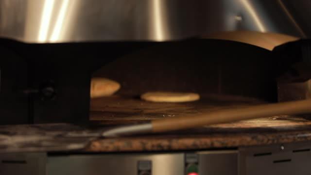 pita bread rotating in hot oven - chleb pita filmów i materiałów b-roll