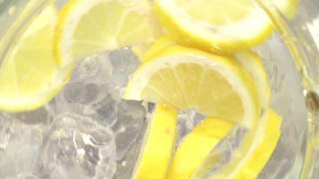 vídeos de stock e filmes b-roll de lançador com água e cubos de gelo e fatias de limão fresco - limonada tradicional